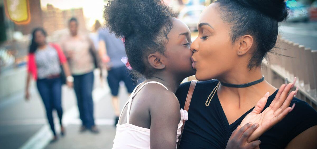 Young daughter kissing mother cheek for COMPI mental health support header