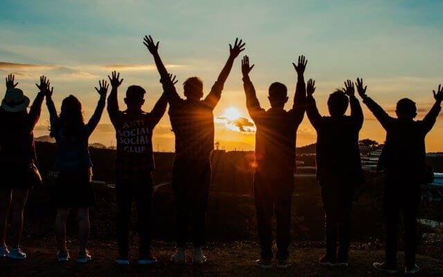 Friends lifting their hands into the sky as sun sets