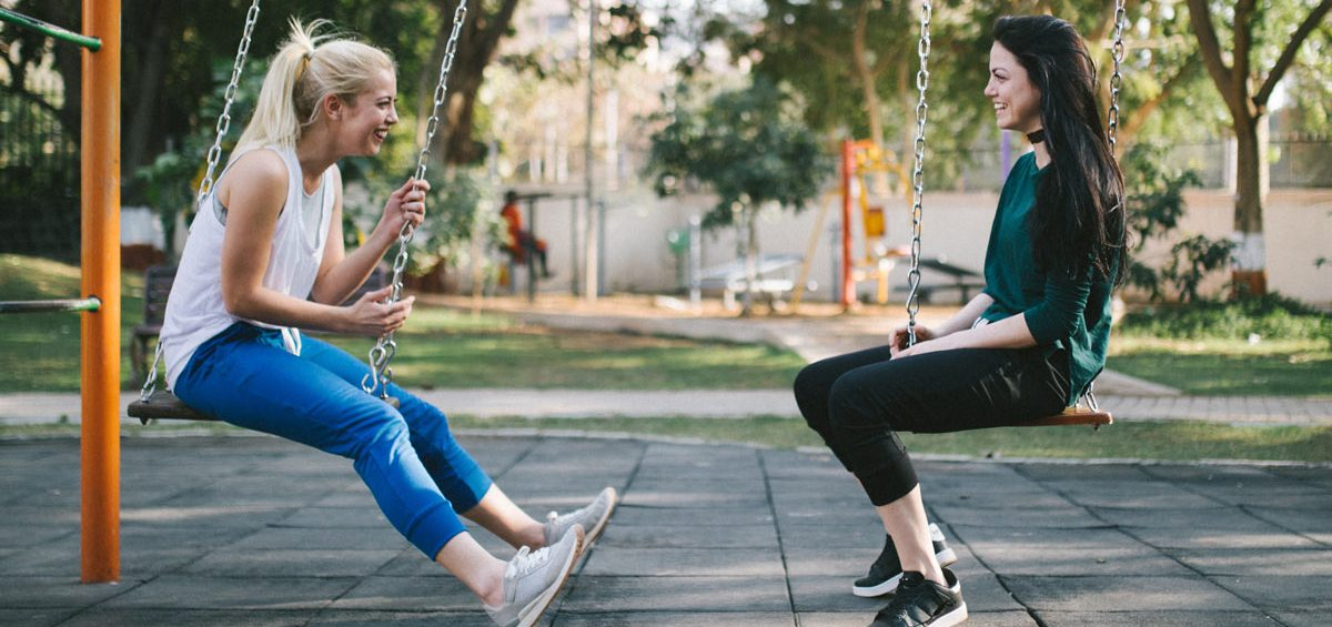 Two teenage girls on swings talking about mental health and positive choices